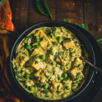 A black bowl of Methi Malai Mutter Paneer on a wooden table with green chilies and a side of naan.