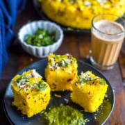 An overhead shot of Nylon Khaman Dhokla served with tea and green chutney