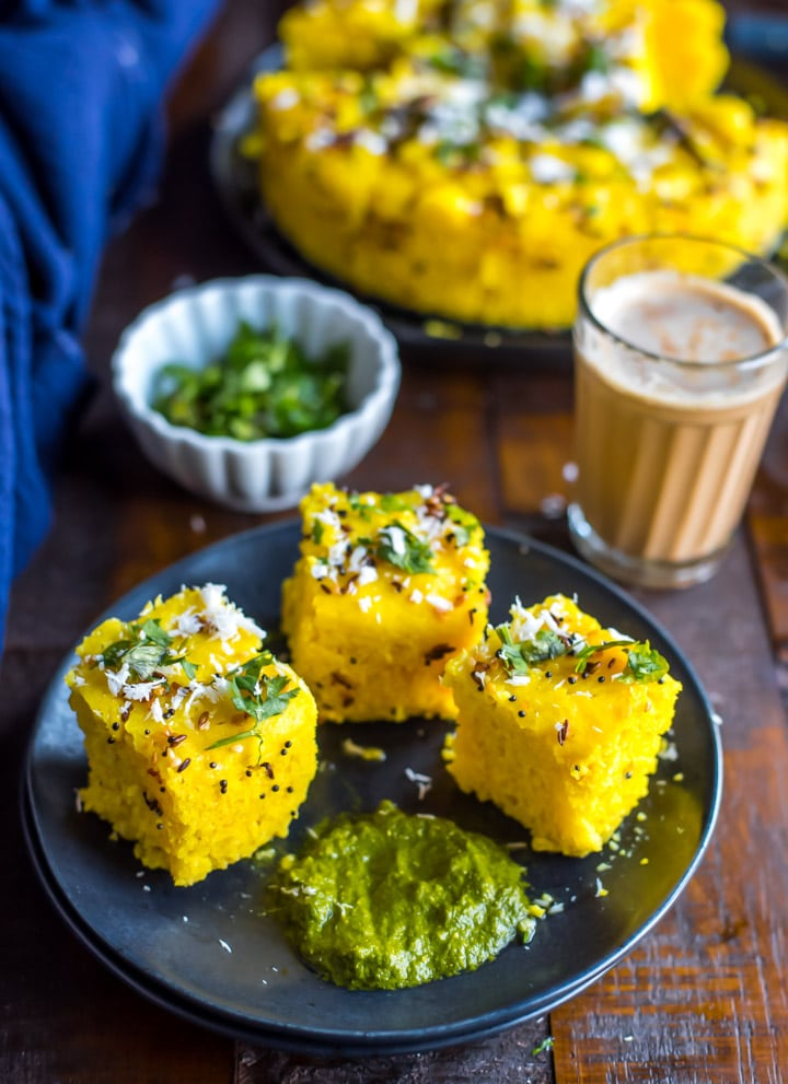 An overhead shot of Nylon Khaman Dhokla served with tea and green chutney