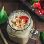 An overhead shot of Banana Spinach Strawberry Smoothie garnished with chopped strawberries and granola