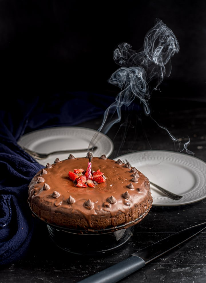 A cakey brownie on a cake stand with a candle blown out and smoke in the air.