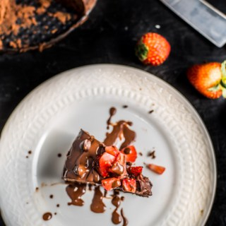 A white plate with a slice of instant pot brownies topped with strawberries.