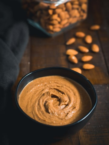 Almond Butter served in a black bowl with almonds placed on the side