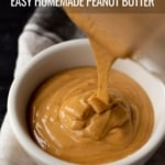 A white bowl with creamy homemade peanut butter being poured into it on white dish towel and the words Easy Homemade Peanut Butter at the top.