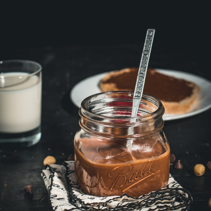 A glass jar filled with chocolate hazelnut spread