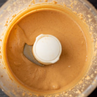 Creamy peanut butter in a food processor with the words.