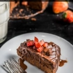 A white plate with a slice of instant pot brownies topped with strawberries with the words Instant Pot Made from Scratch Brownies at the top.