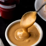 A white bowl of creamy peanut butter with a spoon scooped in the peanut butter.