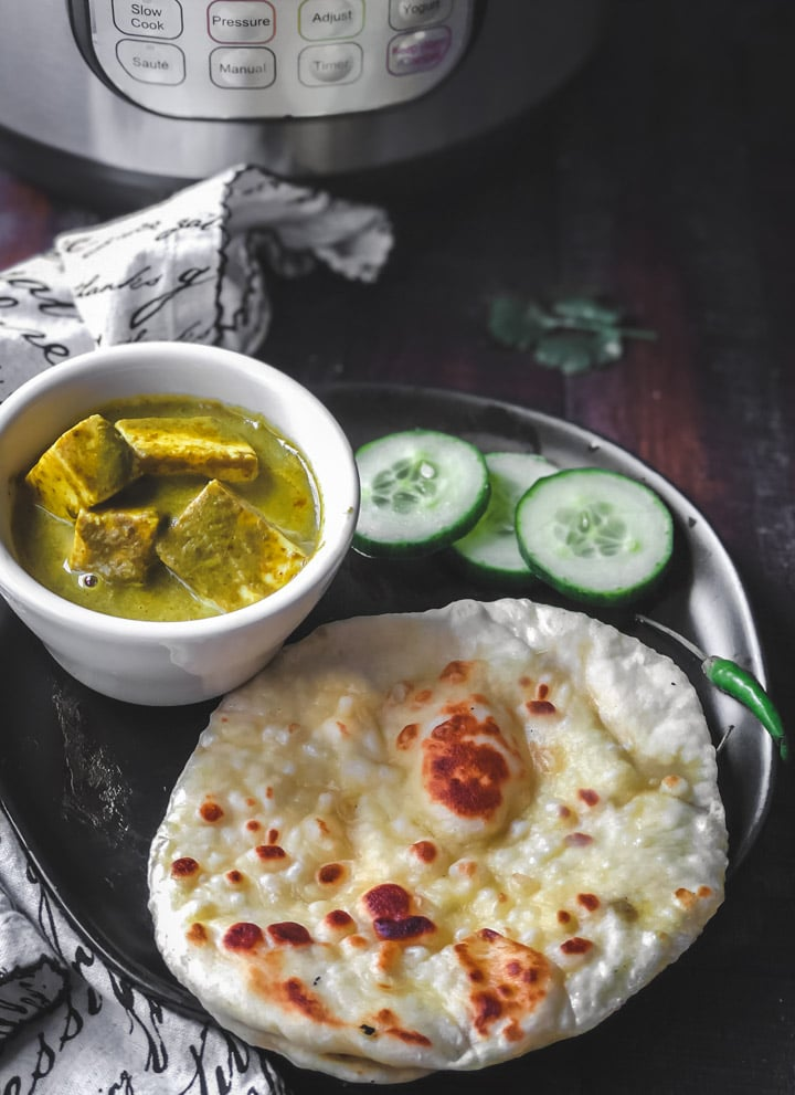 Plain butter naan served with palak paneer and cucumber slices