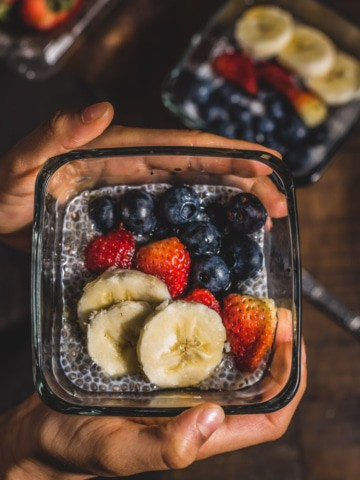 A glass blow with chia pudding topped with banana, strawberry, and blueberry in two hands.
