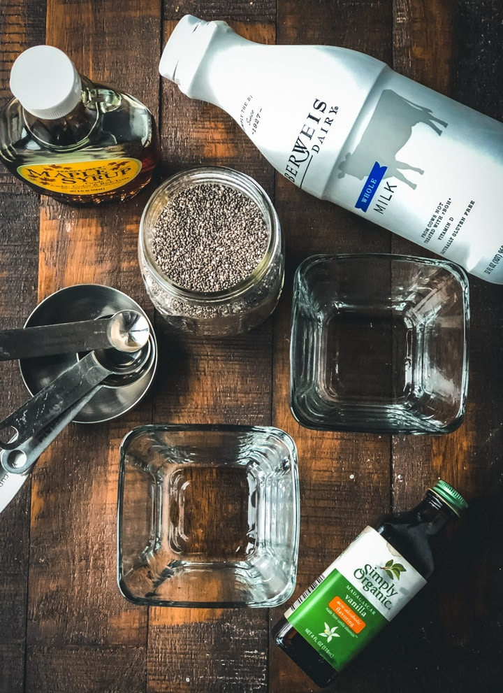 A bottle of milk, maple syrup, chia seeds, vanilla, measuring cups and spoons, and two glass bowls on a wooden table.
