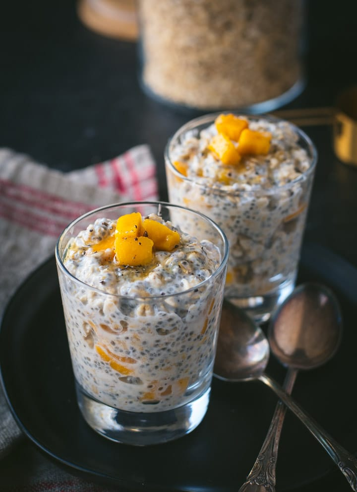 Two glassed filled with Mango overnight oats placed in a black plate