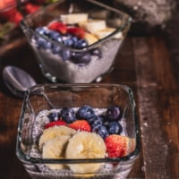 Two glass bowls of vanilla chia pudding topped with banana, strawberry, and blueberry on a wooden table with a spoon in between them and strawberries behind them.