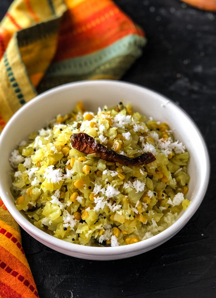 Cabbage Kootu served in white bowl topped with red chily and grated coconut