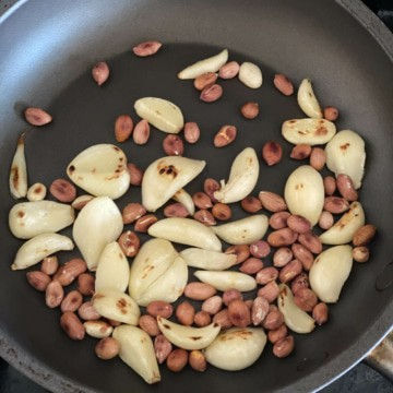 Garlic cloves and peanuts being roasted in a pan