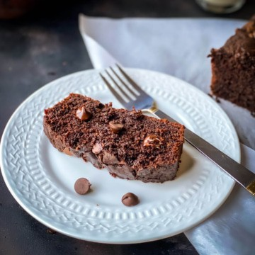 A small white plate with a slice of chocolate zucchini bread and a silver fork next to the slice of moist double chocolate bread.