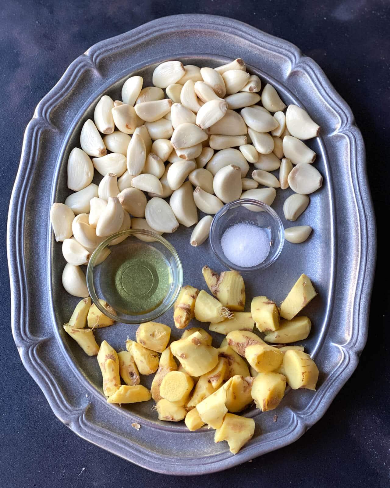 An overhead shot of garlic cloves, ginger, oil and salt