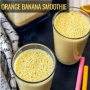 Two glasses of orange julius on a counter with two straws to the right, a cutting board of orange slices in the back, and a blender with orange smoothie in the back left with the words orange banana smoothie in yellow on the left.
