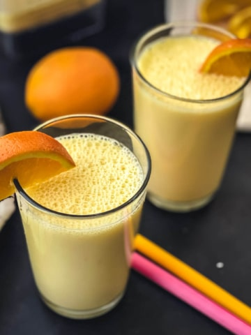 Two glasses of orange smoothie with wedges of orange on the rim, two colorful straws in the middle of the smoothie cups, and an orange in the back.