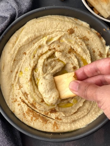 A hand dipping a pita chip into a black bowl filled with creamy instant pot hummus.