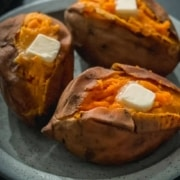 The words Instant Pot in white and Sweet potato in yellow with a blue plate with three sweet potatoes topped with butter.