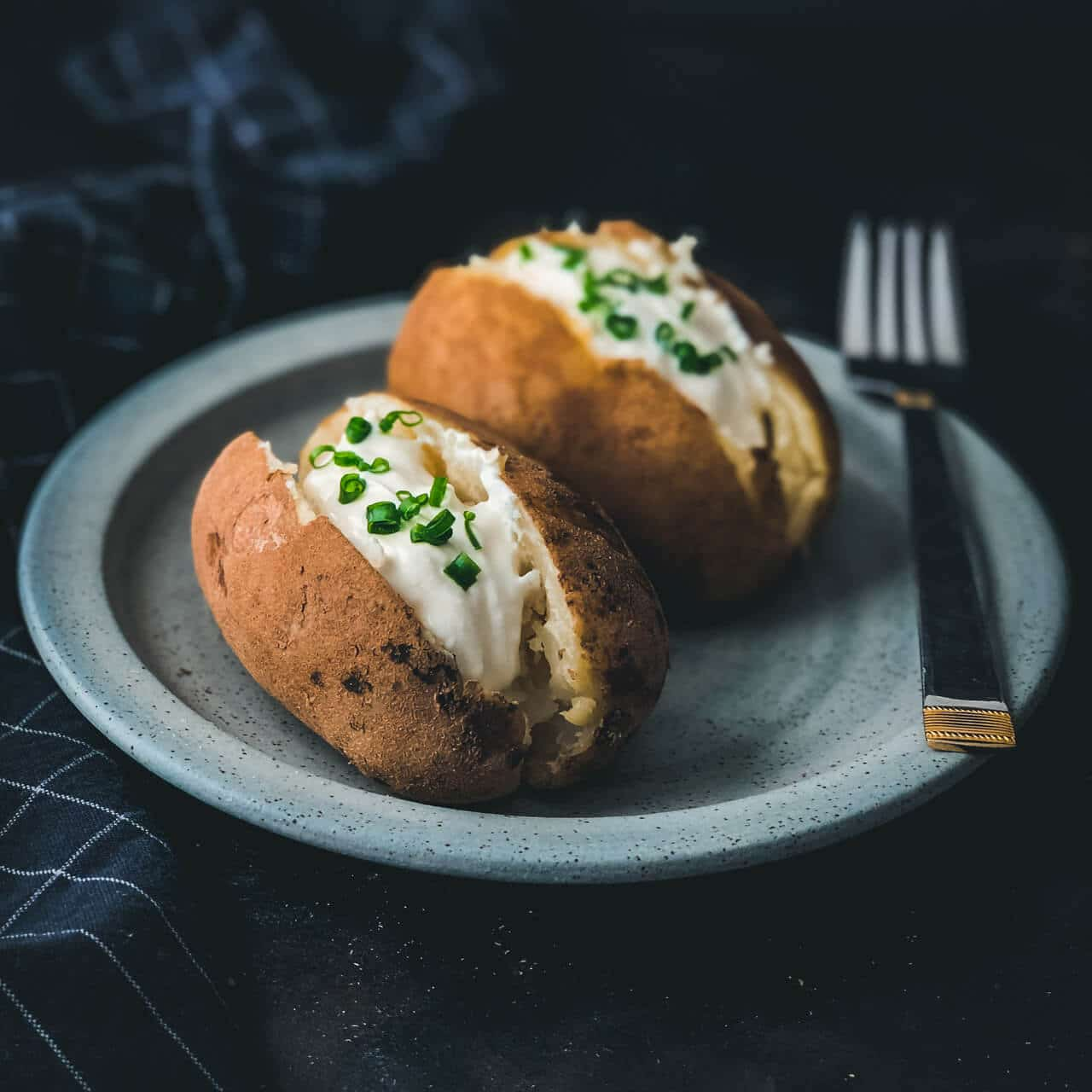 A black counter with a blue plate and two baked potatoes cut down the center vertically and topped with sour cream and chives with a silver fork on the right side of the plate.