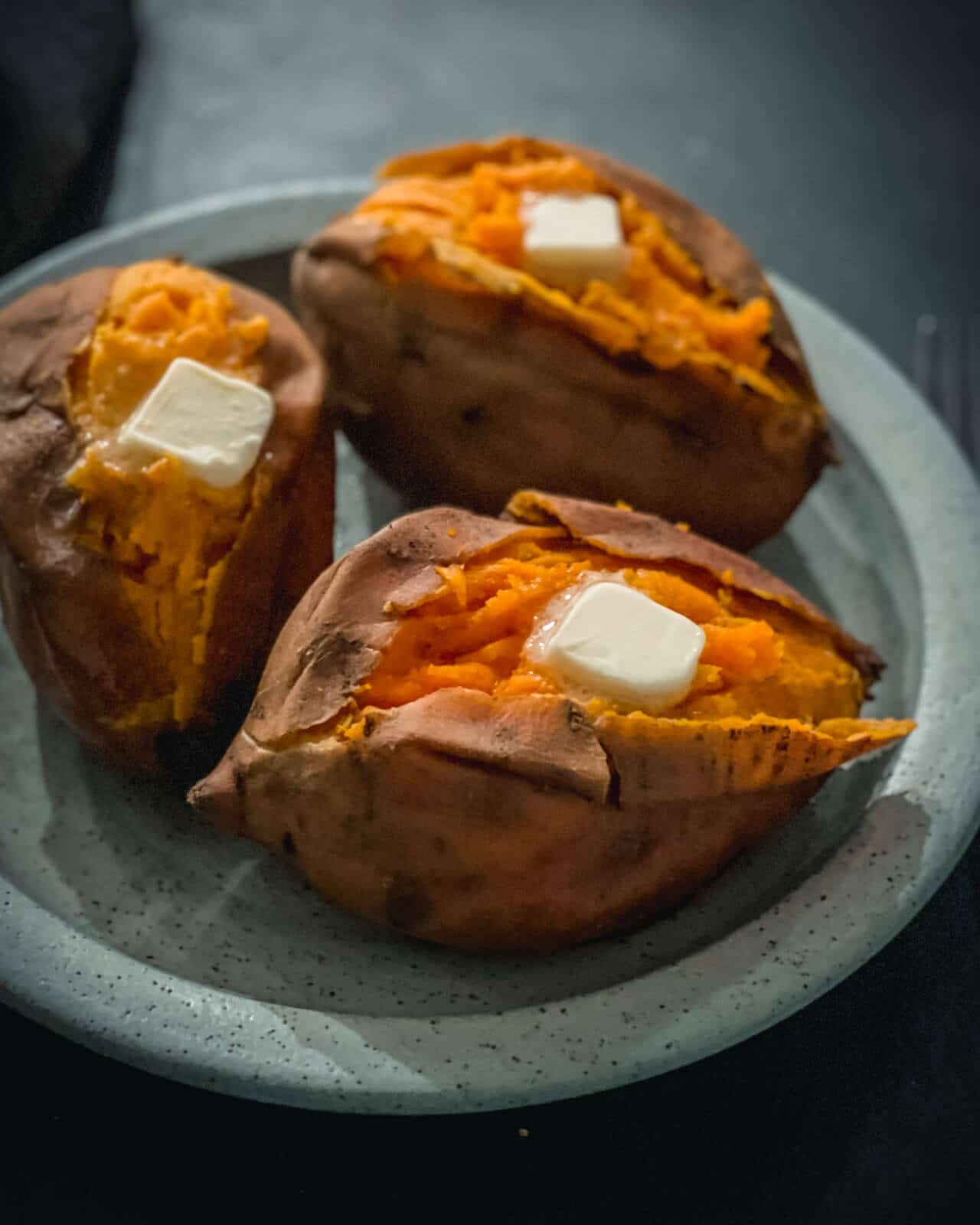 Three baked sweet potatoes cut down the middle with a pad of butter on top on a blue plate.