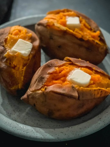 A light blue plate with three baked sweet potatoes with a cut down the middle of each and a pad of butter on top.