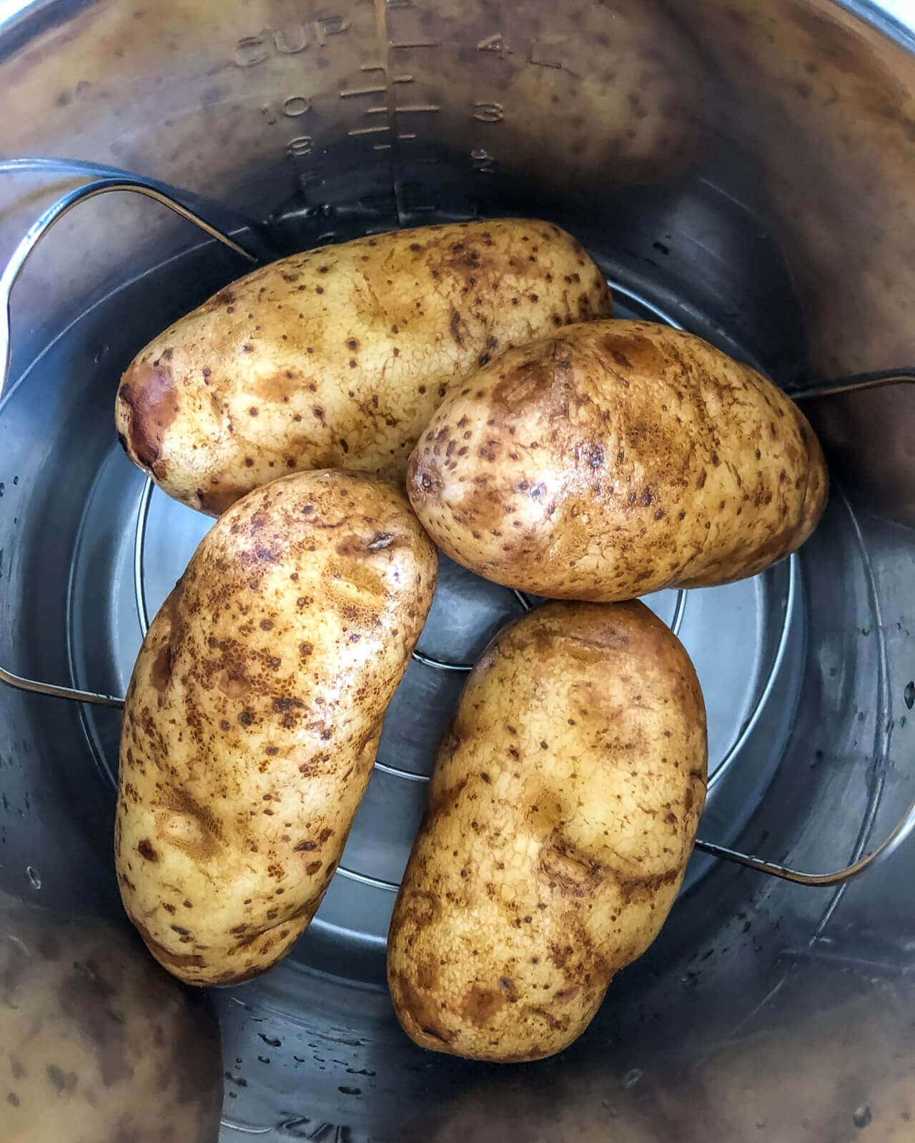 Four potatoes in the instant pot before cooking.