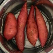Four sweet potatoes on a trivet inside the instant pot.