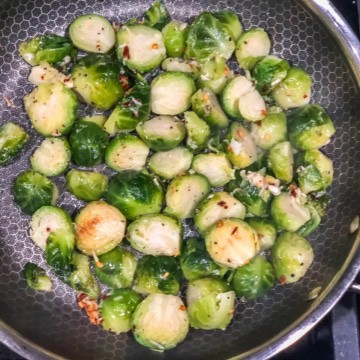 Brussel sprouts being sauteed in a pan