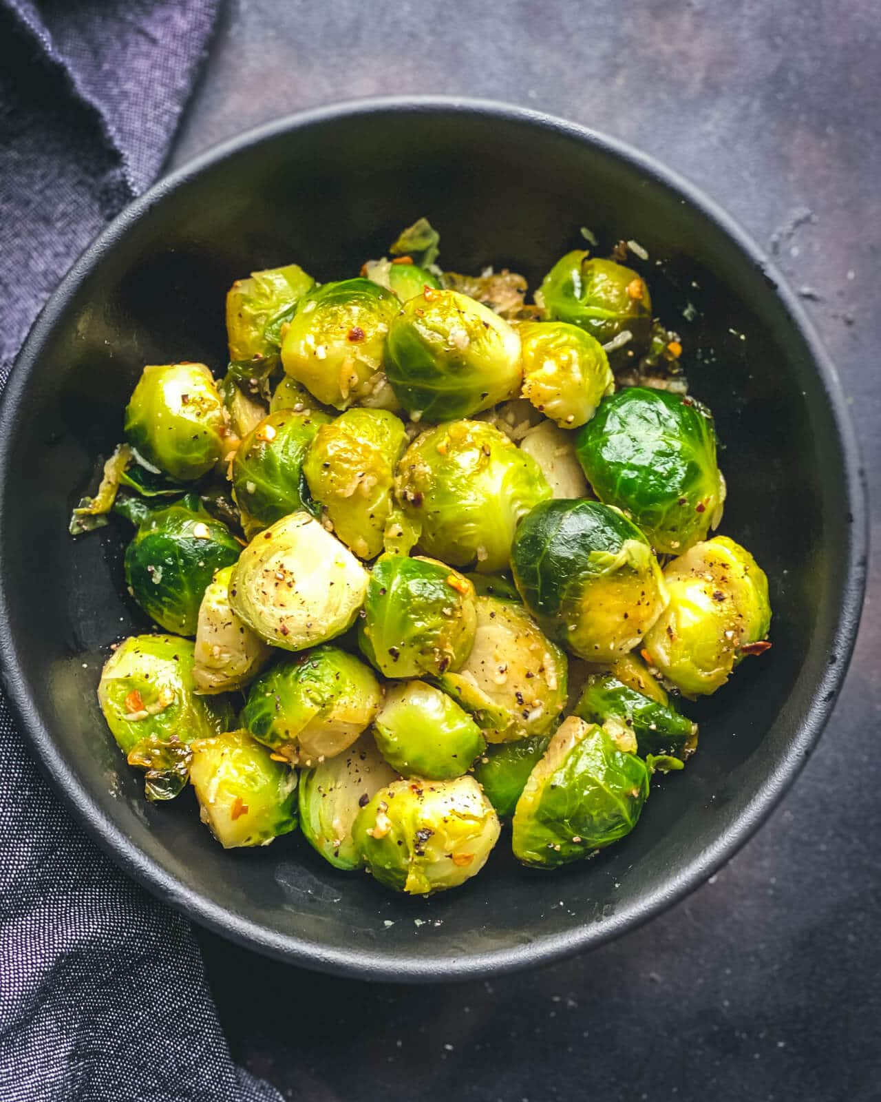 A black bowl with bright green steamed Brussel Sprouts on a grey counter with a grey blue towel to the left.
