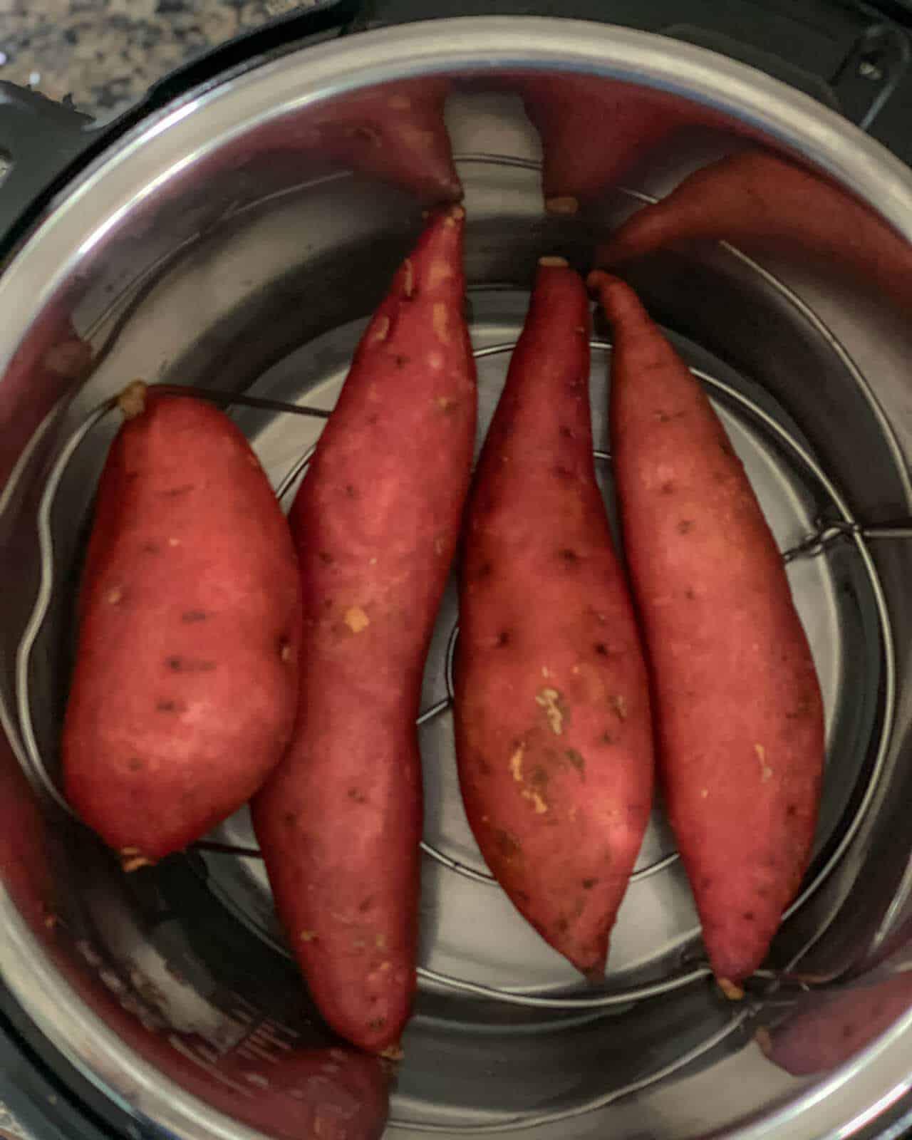 Four sweet potatoes on a trivet inside an instant pot pressure cooker.