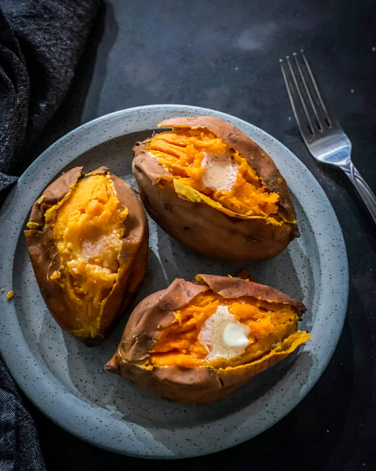 3 sweet potatoes that are split open placed in a grey plate topped with butter