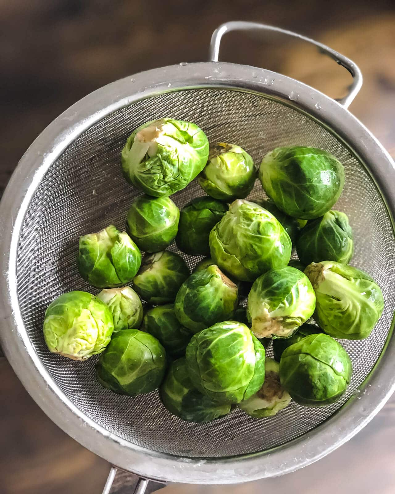 A silver mesh strainer with brussel sprouts over a wooden counter.