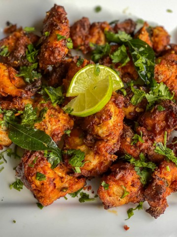 A white plate with an array of crispy chicken 65 topped with cilantro and lemon.