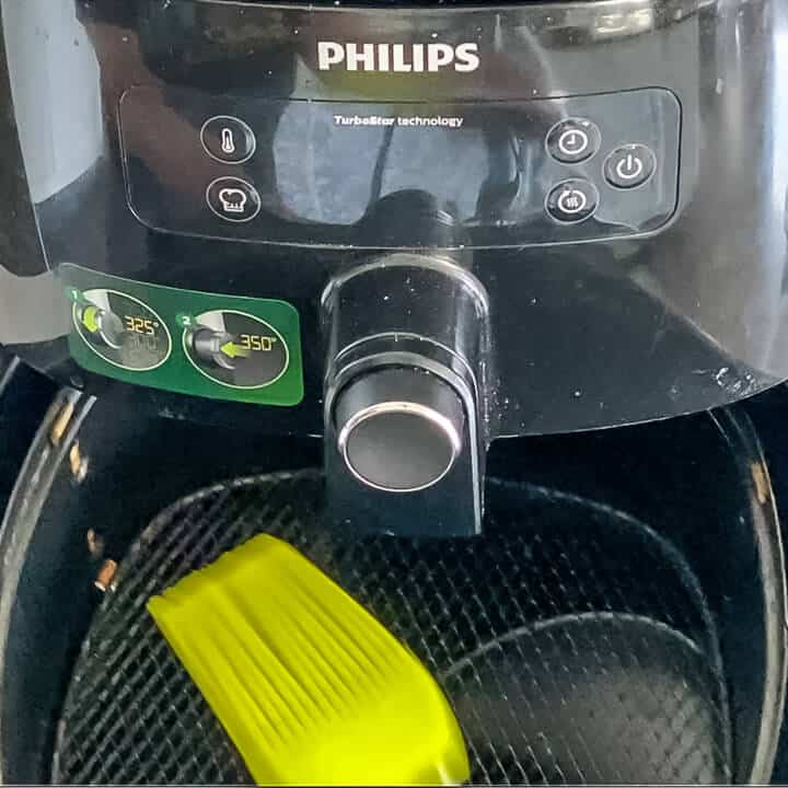 A brush coating the air fryer basket with oil.