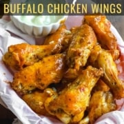A parchment paper lined basket with a stack of buffalo wings in the front and a small bowl of ranch in the back with the words Air Fryer Buffalo Chicken Wings at the top.