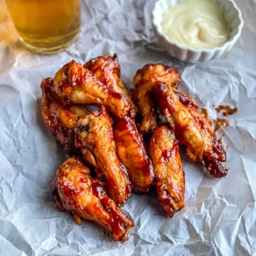 A parchment paper with a stack of chicken wings with a small bowl of ranch to the right and a cold beer in the back left.