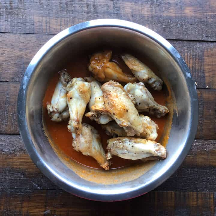 Chicken wings in a bowl with buffalo sauce.