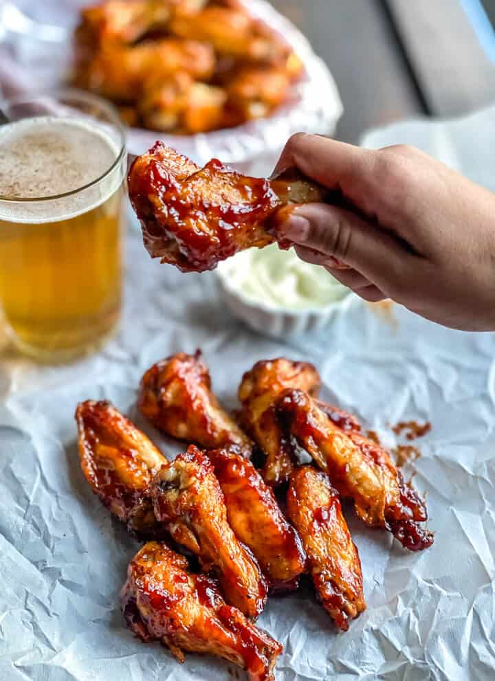 A hand holding a bbq chicken wing over a stack of other wings with a cup of ranch and a glass of beer in the back.