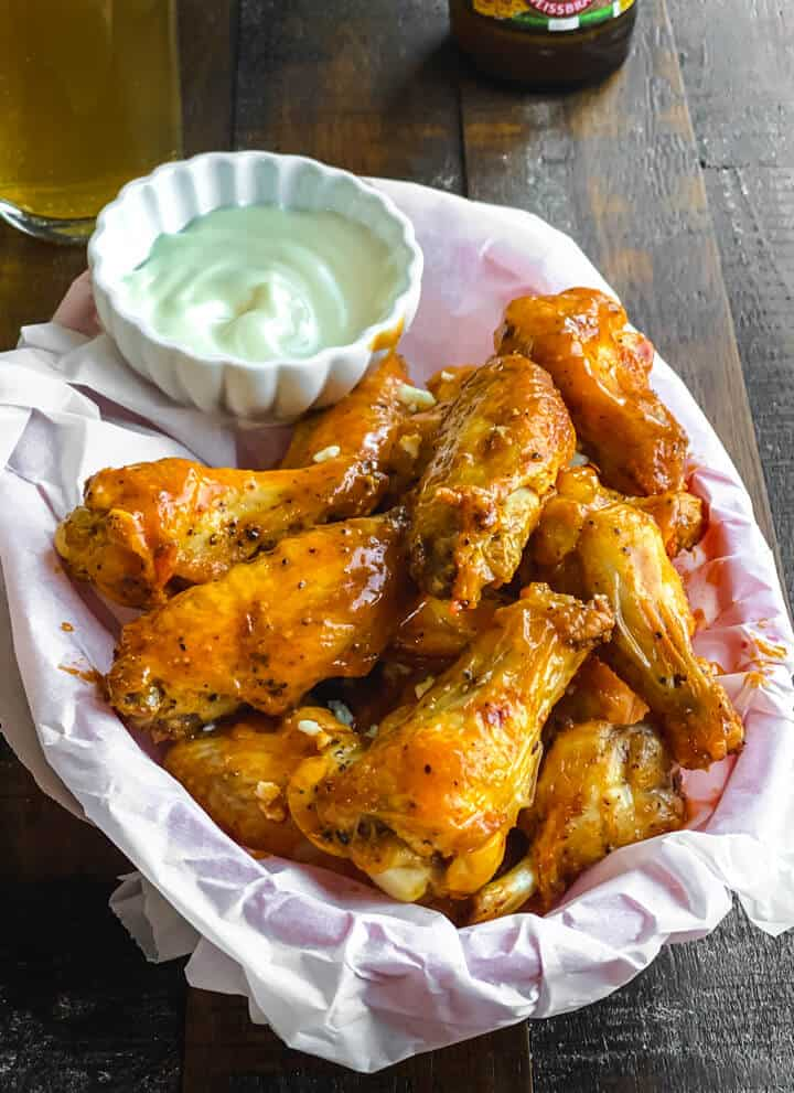 A parchment paper lined basket with a stack of buffalo chicken wings with a small cup of ranch in the back.