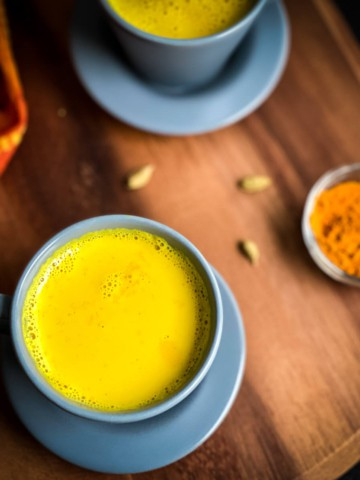A blue mug with golden turmeric latte on a wooden counter with another latte in the back and a small bowl of turmeric to the right.