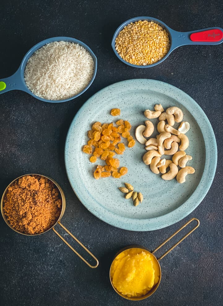 Image of ingredients used in Sweet Pongal - rice, moong dal, powdered jaggery, raisins,cashews, green cardamom and ghee