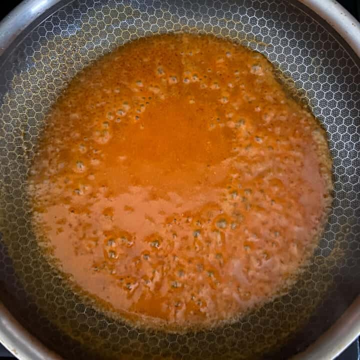 Buffalo sauce melting in a pan.