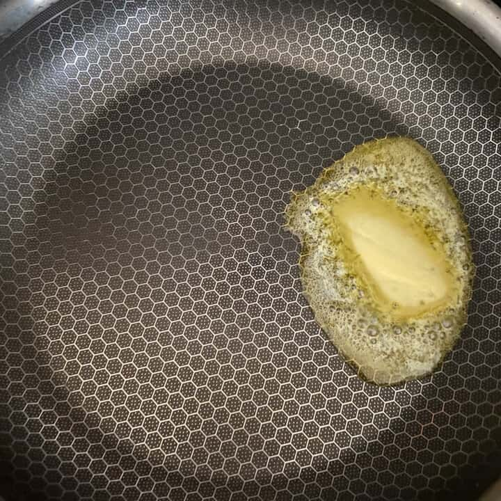 Butter melting in a non-stick skillet.