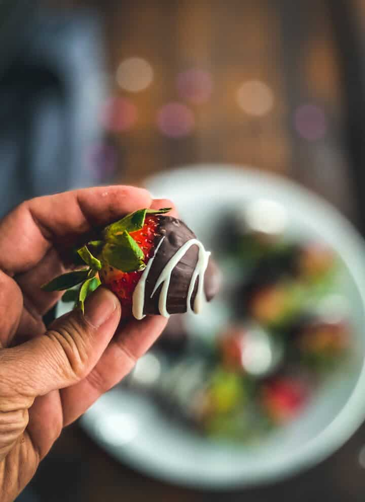 A hand holding a chocolate covered strawberry drizzled with white chocolate in front of a plate of chocolate covered strawberries.