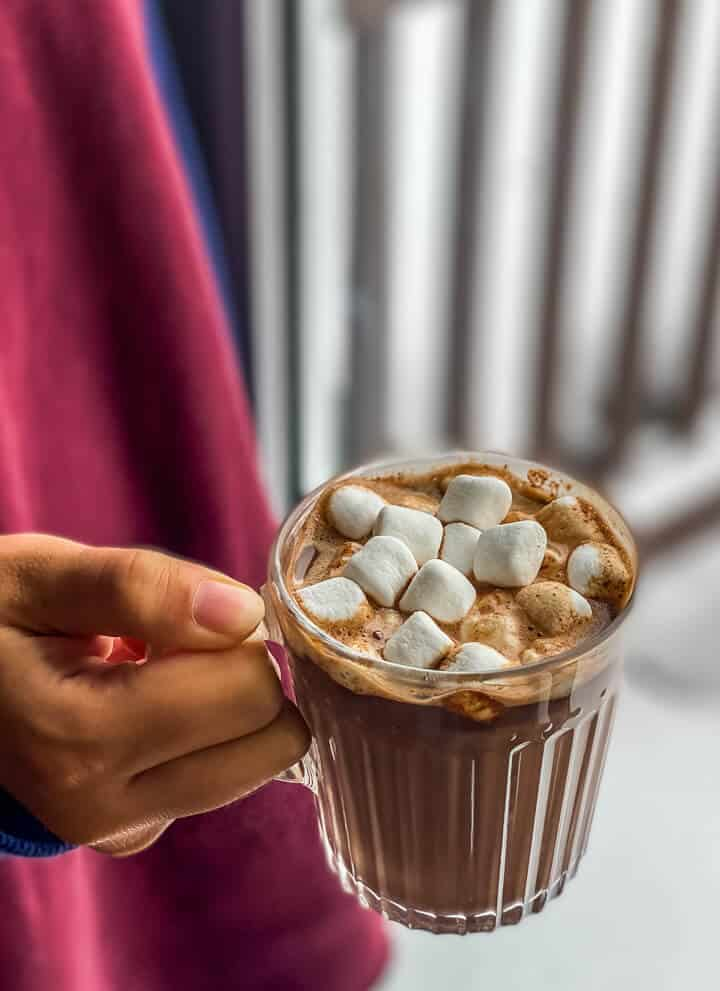 A hand holding a glass mug of hot chocolate topped with marshmallows.