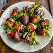 A white plate with chocolate dipped strawberries filling the plate.