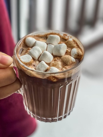 A square picture with a hand holding a clear glass mug of hot chocolate topped with marshmallows.